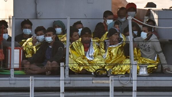 Migrants warmed by emergency blankets arrive on a boat of the Italian Guardia Di Finanza law enforcement agency on May 17, 2021 to disembark on the southern Italian Pelagie Island of Lampedusa. - More than 1,400 migrants arrived on the Italian island of Lampedusa at the weekend, sparking calls from far-right politicians for action to stem the flow, amid fresh moves by Italian authorities against the rescue boats who operate in the central Mediterranean. - Sputnik International