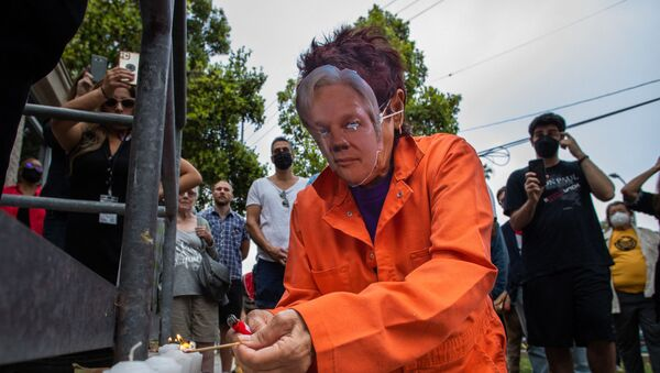 A woman wearing an orange jumpsuit and Julian Assange mask, lights a candle during a Free Julian Assange rally outside the Oakwood Community Center in Venice, Calif. on June 27, 2021, as part of a national tour to raise awareness of Assange as a threat to press freedom.  - Sputnik International