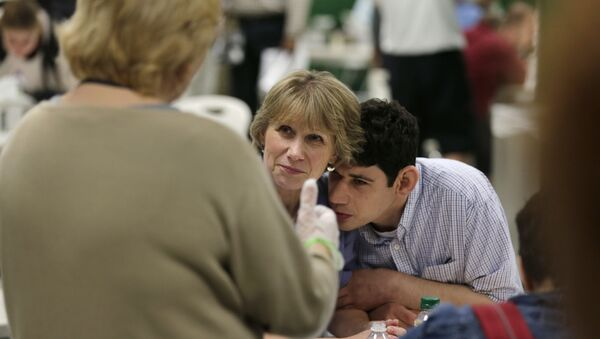 In this August 13, 2014 photograph, Andrew Goldberg rests his head on the shoulder of his mother Louisa as they listen to a therapist in the school cafeteria at the Judge Rotenberg Educational Center in Canton, Massachusetts.  Andrew, who was born with a developmental disorder, wears a electrical shocking device to control violent episodes.  - Sputnik International