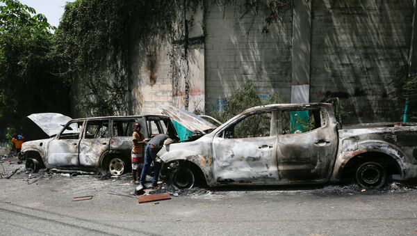 Children look for metal pieces in cars burnt by locals after a firefight between police and the suspected assassins of President Jovenel Moise who was shot dead early Wednesday at his home, in Port-au-Prince, Haiti July 8, 2021. - Sputnik International