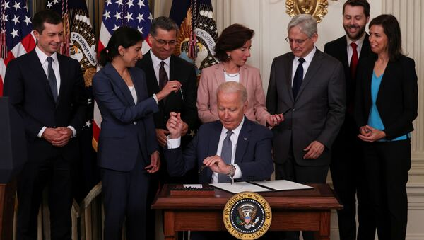 U.S. President Joe Biden hands a pen to Lina Khan, chair of the Federal Trade Commission, while signing an executive order on promoting competition in the American economy, as members of his Cabinet standby in the State Dining Room at the White House in Washington U.S., July 9, 2021. - Sputnik International