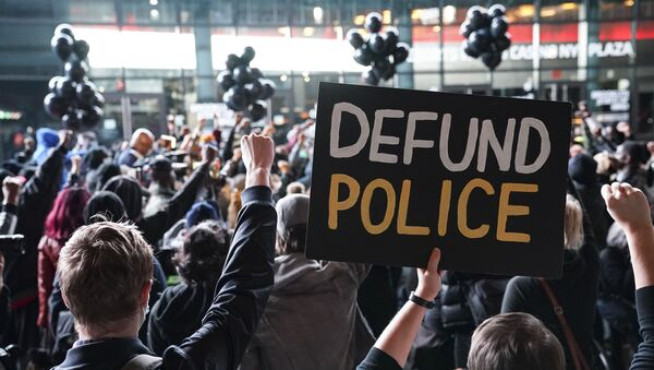 In this 14 October 2020 file photo, a protester holds a sign that reads Defund Police during a rally for the late George Floyd outside Barclays Center in New York - Sputnik International
