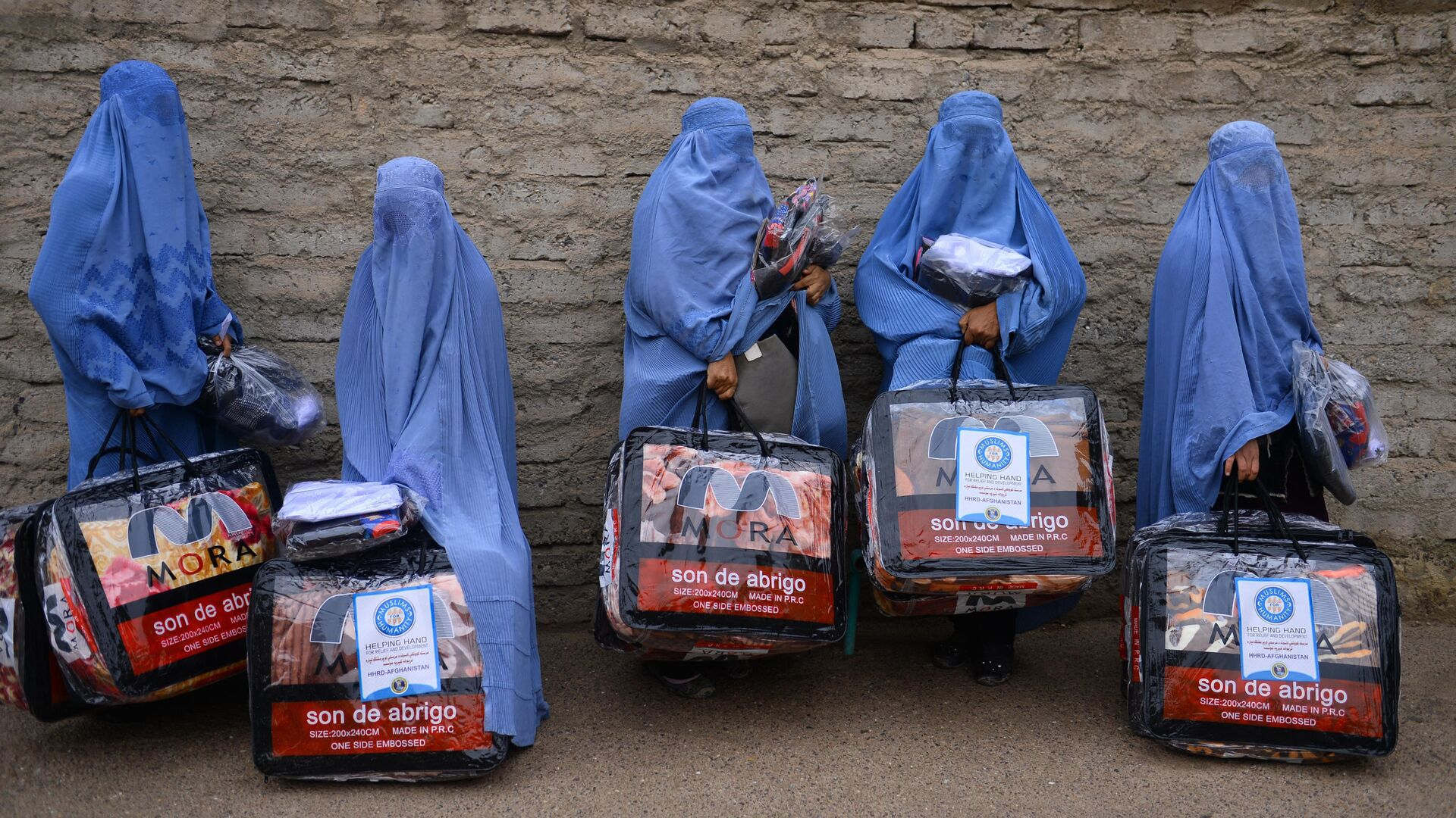 In this photograph taken on December 19, 2019, Afghan burqa-clad women stand with aid items recieved from a charity in Herat. - Sputnik International, 1920, 05.09.2021