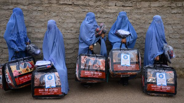 In this photograph taken on December 19, 2019, Afghan burqa-clad women stand with aid items recieved from a charity in Herat. - Sputnik International