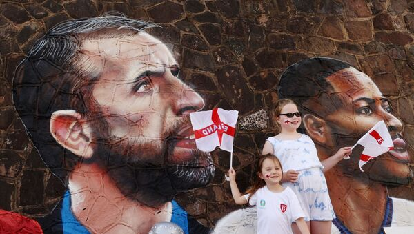 Soccer Football - England fans pose for a photograph in front of a giant mural created by street artist Nathan Parker of Gareth Southgate, Harry Kane and Raheem Sterling ahead of the Euro 2020 final against Italy - Bullring, Nuneaton, Britain - July 10, 2021 - Sputnik International
