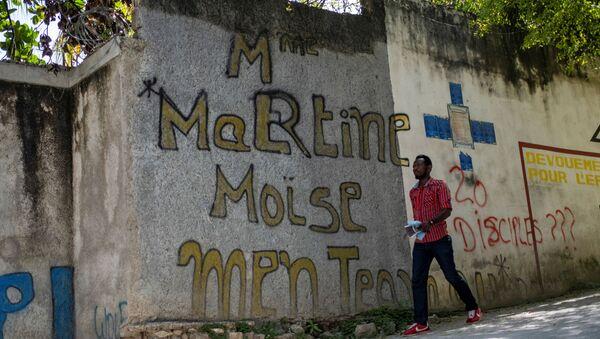 A man walks past a graffiti that reads Martine Moise near the house where President Jovenel Moise was assassinated, in Port-au-Prince, Haiti July 11, 2021. - Sputnik International