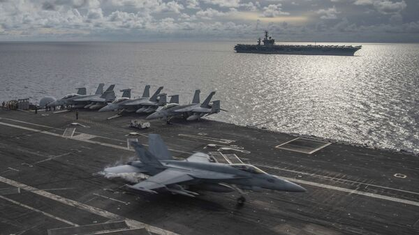 In this photo provided by U.S. Navy, an F/A-18E Super Hornet lands on the flight deck of the USS Ronald Reagan (CVN 76), as USS Nimitz (CVN 68) steams alongside in the South China Sea, Monday, July 6, 2020. - Sputnik International