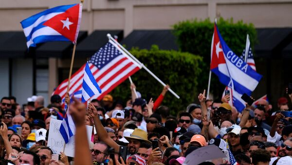 Emigres in Little Havana wave American and Cuban flags as they react to reports of protests in Cuba against the deteriorating economy, in Miami, Florida, U.S., July 11, 2021 - Sputnik International