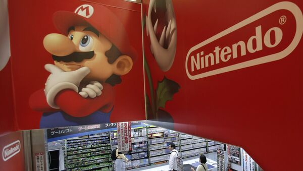 FILE - In this May 7, 2014, file photo, shoppers walk under the logo of Nintendo and Super Mario character, left, at an electronics store in Tokyo. Japanese Prime Minister Shinzo Abe's appearance as Super Mario in the Rio Olympics closing ceremonies on Sunday, Aug. 21, 2016, was a crowd-pleasing reminder of how much the game helped spur on the videogame revolution in the U.S. and globally. - Sputnik International