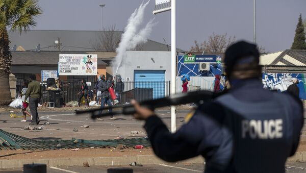 People throw stones at police as they attempt looting at Letsoho Shopping Centre in Katlehong, east of Johannesburg, South Africa, Monday, July 12, 2021. - Sputnik International