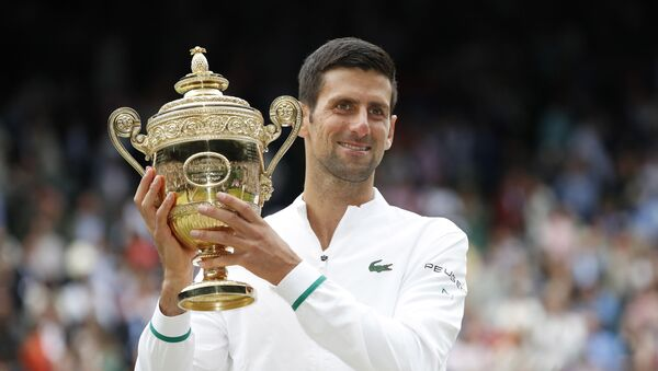 Tennis - Wimbledon - All England Lawn Tennis and Croquet Club, London, Britain - July 11, 2021 Serbia's Novak Djokovic celebrates with the trophy after winning his final match against Italy's Matteo Berrettini - Sputnik International