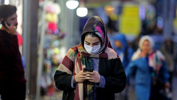 An Iranian woman wearing a protective mask checks her mobile telephone as she walks in a street in the capital Tehran on February 20,2020 (Photo by ATTA KENARE / AFP) - Sputnik International