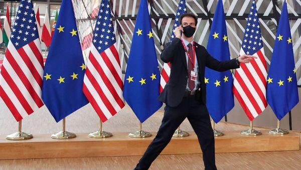 A security guard walks near EU and U.S. flags, before the EU-US summit, in Brussels, Belgium June 15, 2021 - Sputnik International