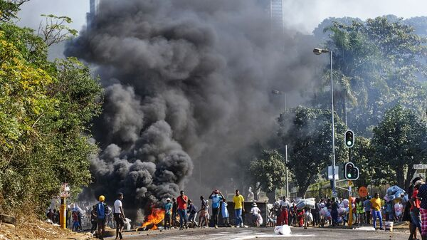 Looters outside a shopping centre alongside a burning barricade in Durban, South Africa, Monday July 12, 2021 - Sputnik International