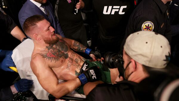 (FILES) In this file photo Conor McGregor of Ireland is carried out of the arena on a stretcher after injuring his ankle in the first round of his lightweight bout against Dustin Poirier during UFC 264: Poirier v McGregor 3 at T-Mobile Arena on July 10, 2021 in Las Vegas, Nevada.  - Sputnik International