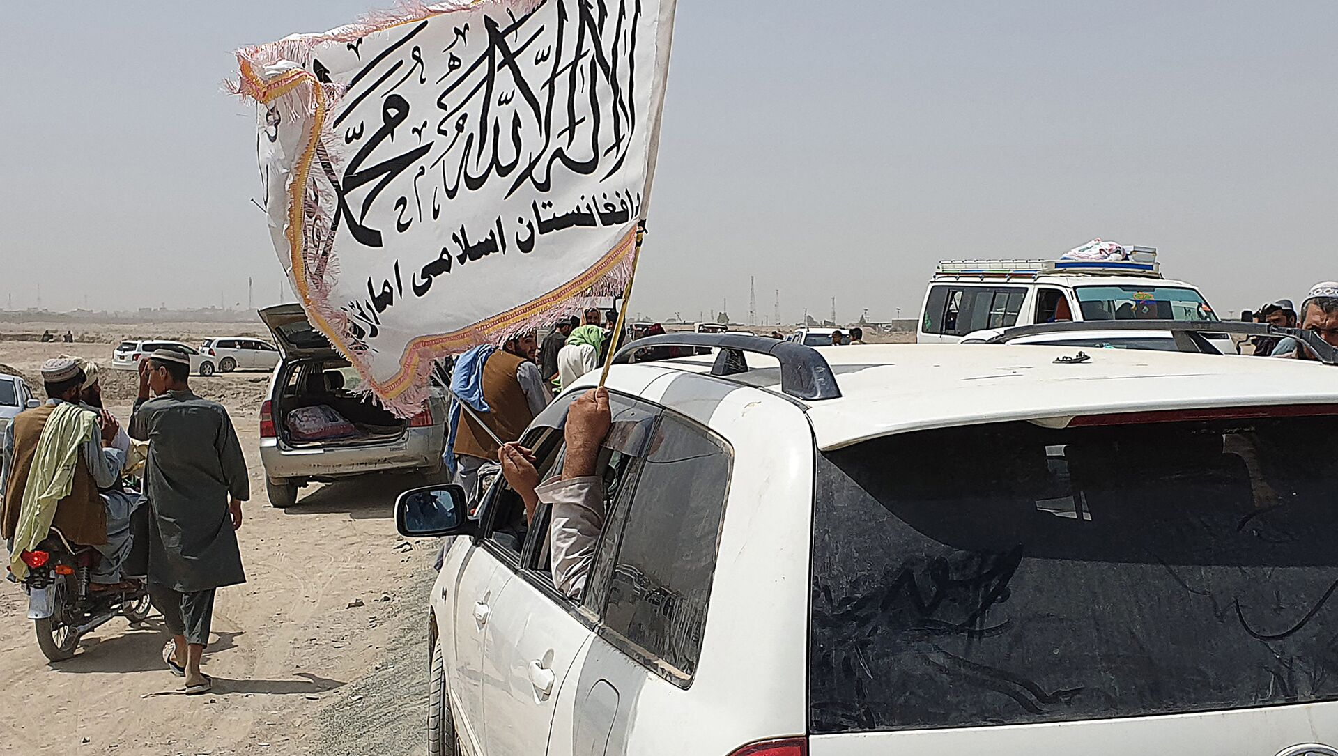 People wave a Taliban flag as they drive through the Pakistani border town of Chaman on July 14, 2021, after the Taliban claimed they had captured the Afghan side of the border crossing of Spin Boldak along the frontier with Pakistan - Sputnik International, 1920, 04.08.2021