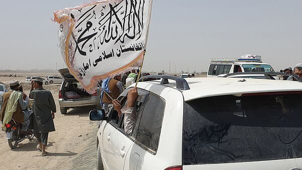 People wave a Taliban flag as they drive through the Pakistani border town of Chaman on July 14, 2021, after the Taliban claimed they had captured the Afghan side of the border crossing of Spin Boldak along the frontier with Pakistan - Sputnik International