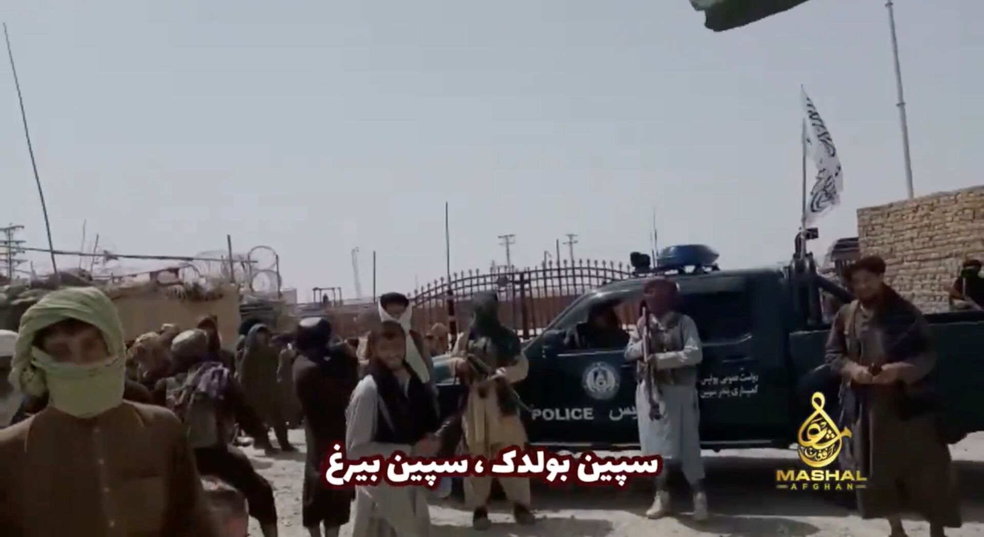 People stand in front of a vehicle as an Islamic Emirate of Afghanistan and a Pakistan's flag flutter in front of the friendship gate of Afghanistan and Pakistan at the Wesh-Chaman border crossing, Spin Boldak, Afghanistan July 14, 2021, in this screen grab obtained from a video - Sputnik International, 1920, 07.09.2021