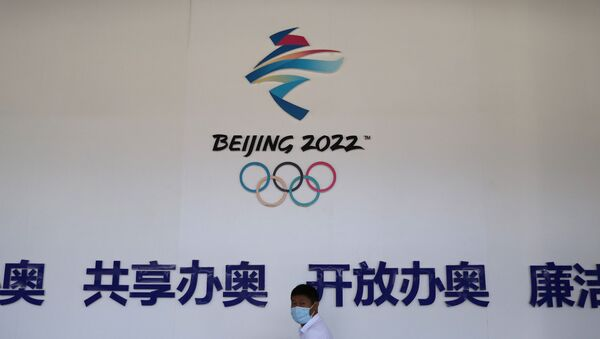 A man walks past a board with a sign of Beijing 2022 Winter Olympic Games at an exhibition hall during an organised media tour to venues of the Games in Zhangjiakou, Hebei province, China July 14, 2021 - Sputnik International