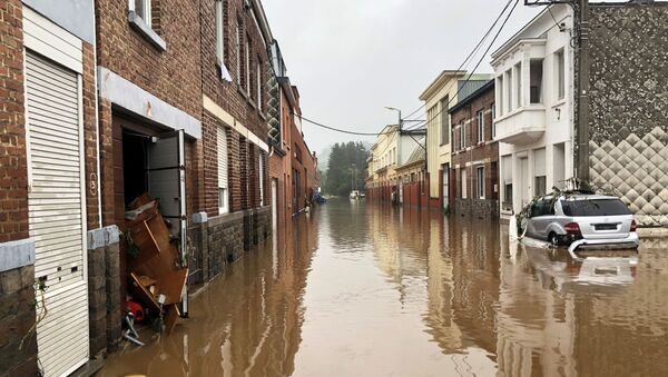A partially-submerged car is seen on a flooded street in Pepinster, Belgium July 15, 2021 - Sputnik International