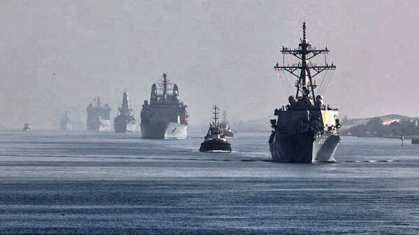 This handout image provided by the official Twitter account of Commodore Steve Moorhouse, Royal Navy, Commander of the UK Carrier Strike Group on July 6, 2021 shows a view of the vessels of the strike group sailing behind the Royal Navy's HMS Queen Elizabeth aircraft carrier through Egypt's Suez Canal. - Sputnik International