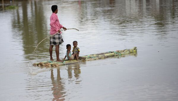 An Indian flood affected man rows a makeshift banana raft with two children in Gagolmari village, Morigaon district, Assam, India, Tuesday, July 14, 2020 - Sputnik International