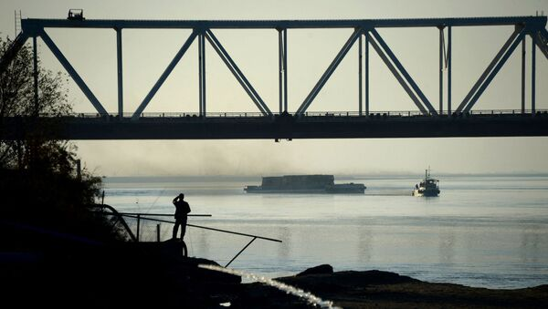 In this photograph taken on November 30, 2015, an Afghan man watches a ship travel along the Amu River on the border of Afghanistan and Uzbekistan, about 75 kms north of Mazar-i-Sharif.  - Sputnik International