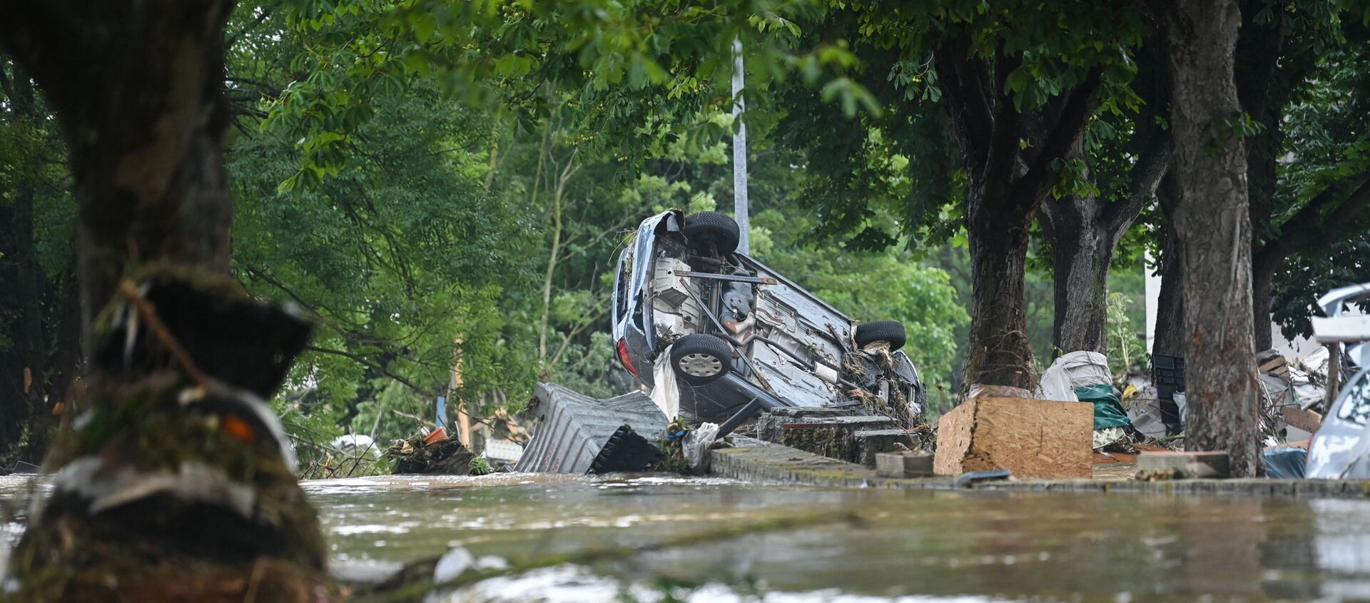 A car stands upside down near floating water in Iversheim, near Bad Muenstereifel, western Germany, on July 16, 2021, following heavy rains and floods. - The death toll from devastating floods in Europe soared to at least 126 on July 16, most in western Germany where emergency responders were frantically searching for missing people. - Sputnik International, 1920, 16.07.2021