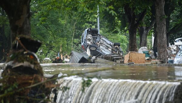 A car stands upside down near floating water in Iversheim, near Bad Muenstereifel, western Germany, on July 16, 2021, following heavy rains and floods. - The death toll from devastating floods in Europe soared to at least 126 on July 16, most in western Germany where emergency responders were frantically searching for missing people. - Sputnik International
