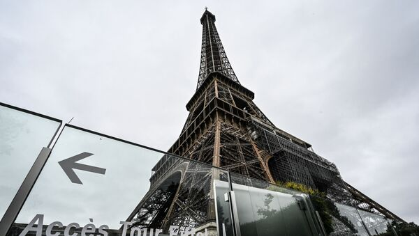This picture taken on July 16, 2021, in Paris shows the Eiffel Tower and its protective wall. - The Eiffel Tower reopened to visitors on July 16, 2021, after nine months of shutdown caused by the Covid pandemic. Up to 13,000 people per day will be allowed to take the elevators to the top and take in the views over the French capital, down from 25,000 in the pre-Covid era.  - Sputnik International