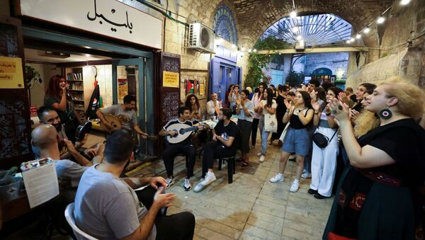 People clap as they watch musicians perform during a happening, part of an initiative launched by young Palestinians aiming to revive Nazareth's old city market, in Nazareth, northern Israel July 11, 2021.  - Sputnik International