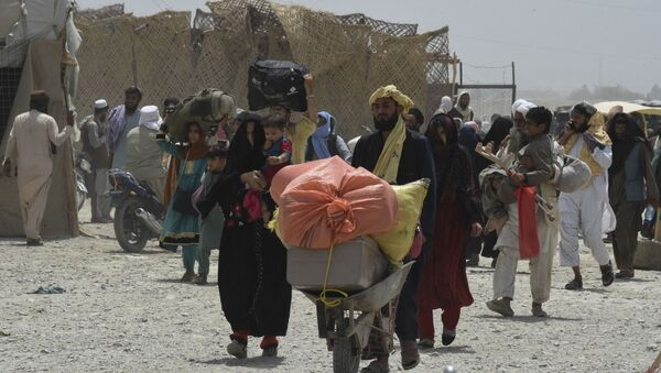 People walk towards a border crossing point in Pakistan's border town of Chaman on July 17, 2021, after Pakistan partially reopened its southern crossing with Afghanistan, shut off since the Taliban seized control of the strategic border town on the other side.  - Sputnik International