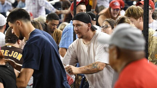 Fans run onto the field for cover after shots are heard from a shooting outside the stadium that sent players and fans seeking shelter during a baseball game between the San Diego Padres and the Washington Nationals at Nationals Park on July 17, 2021 in Washington, DC.   - Sputnik International