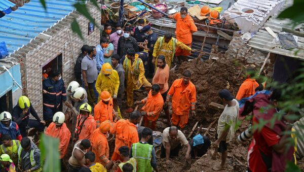 National Disaster Response Force (NDRF) and other rescue team personnel inspect the site of the landslide in a slum area where 18 people were killed after several homes were crushed by a collapsed wall and a landslide triggered by heavy monsoon rains in Mumbai on 18 July 2021. - Sputnik International