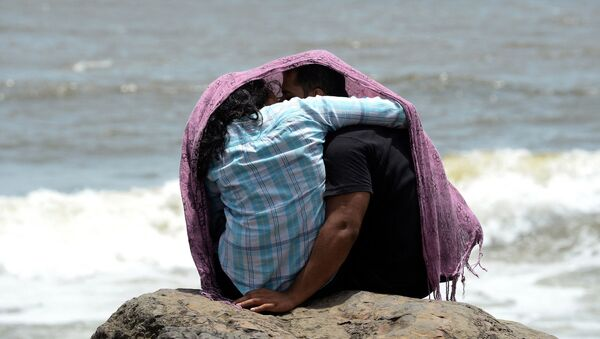A young couple sit together on a rocky outcrop off the Arabian sea in Mumbai on July 3, 2015 - Sputnik International