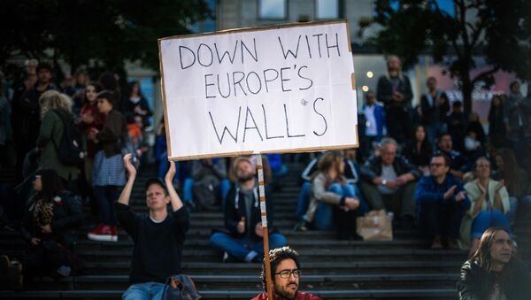 A man holds a sign as he takes part in a demonstration in solidarity with migrants seeking asylum in Europe after fleeing their home countries in Stockholm on September 12, 2015. - Sputnik International