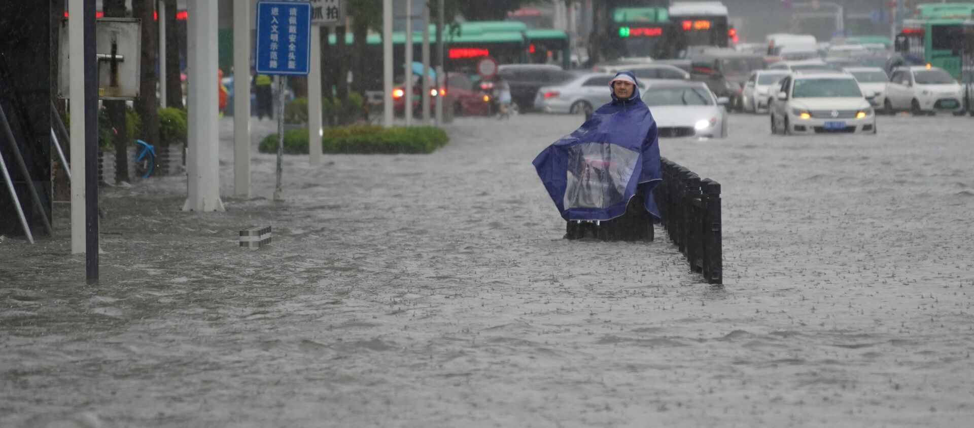 A resident wearing a rain cover stands on a flooded road in Zhengzhou, Henan province, China July 20, 2021. - Sputnik International, 1920, 20.07.2021