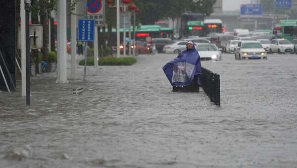 A resident wearing a rain cover stands on a flooded road in Zhengzhou, Henan province, China July 20, 2021. - Sputnik International