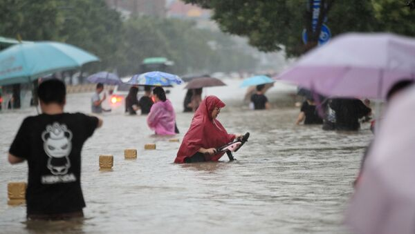 Residents wade through floodwaters on a flooded road amid heavy rainfall in Zhengzhou, Henan province, China July 20, 2021. Picture taken July 20, 2021.  - Sputnik International