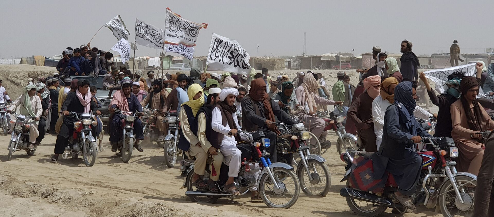 Supporters of the Taliban carry the Taliban's signature white flags in the Afghan-Pakistan border town of Chaman, Pakistan, Wednesday, July 14, 2021 - Sputnik International, 1920, 01.08.2021