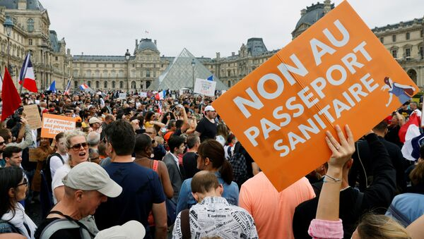 Demonstrators attend a protest against the new measures announced by French President Emmanuel Macron to fight the coronavirus disease (COVID-19) outbreak, in Paris, France, July 17, 2021. - Sputnik International