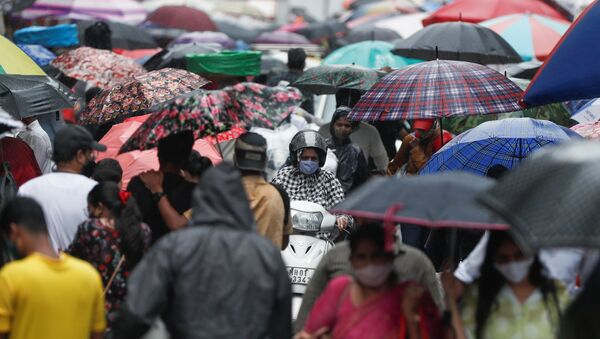 A woman rides a scooter through a crowded market on a rainy day amidst the spread of the coronavirus disease (COVID-19) in Mumbai, India, 14 July 2021.  - Sputnik International