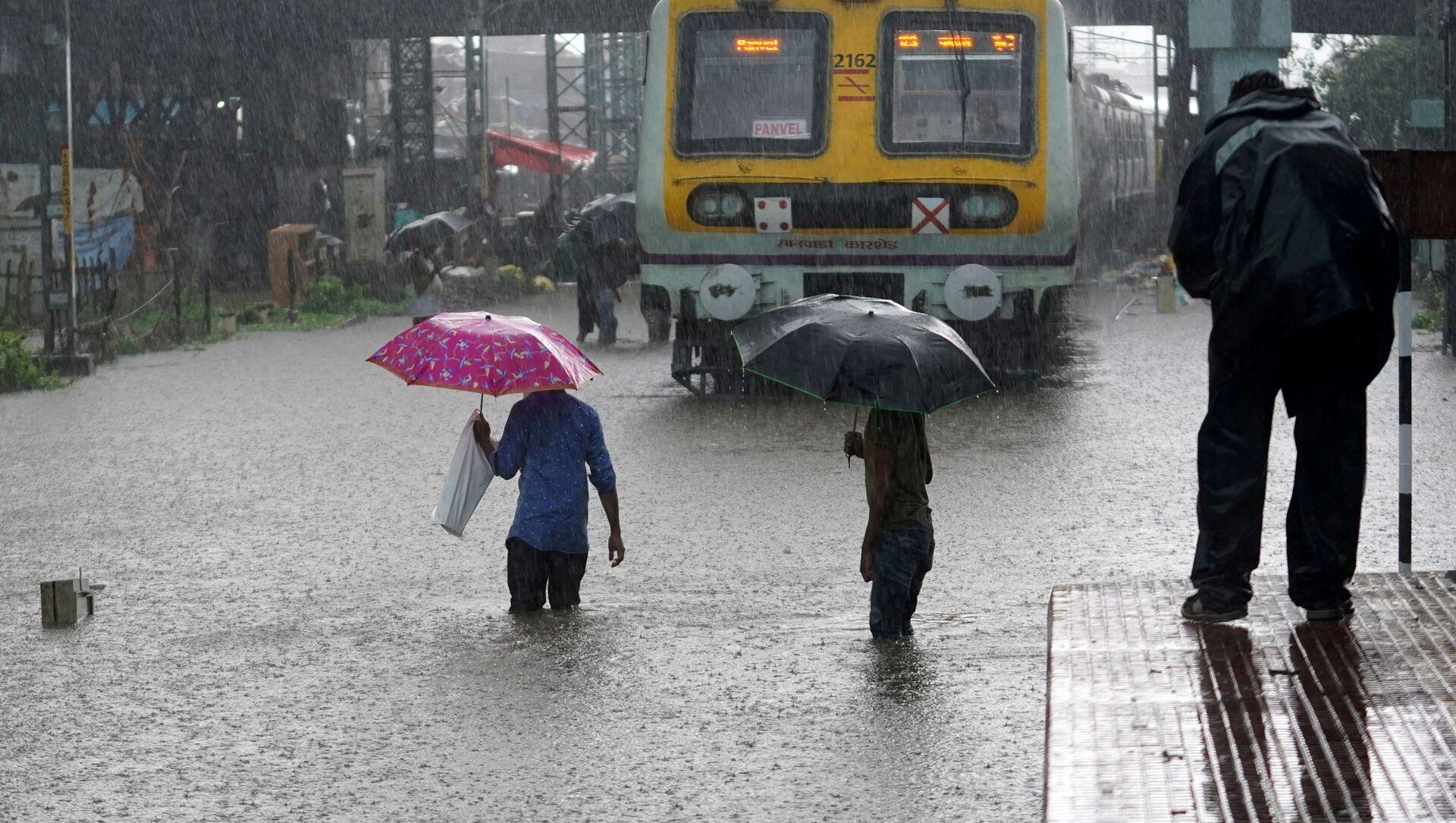 People cross inundated railway tracks next to a parked passenger train during heavy monsoon rains in Mumbai, India, June 9, 2021 - Sputnik International, 1920, 24.07.2021