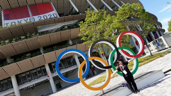 A woman poses in front of the National Stadium, the main stadium of Tokyo 2020 Olympics and Paralympics in Tokyo, Japan July 23, 2021. - Sputnik International