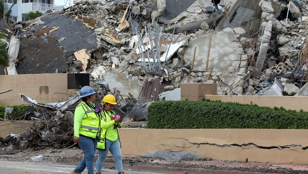 Rescue workers walk past debris after the managed demolition of the remaining part of Champlain Towers South complex as search-and-rescue efforts continue in Surfside, Florida, 6 July 2021. - Sputnik International