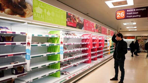 FILE PHOTO: A man stands next to shelves empty of fresh meat in a supermarket, as the number of worldwide coronavirus cases continues to grow,  in London, Britain, March 15, 2020 - Sputnik International