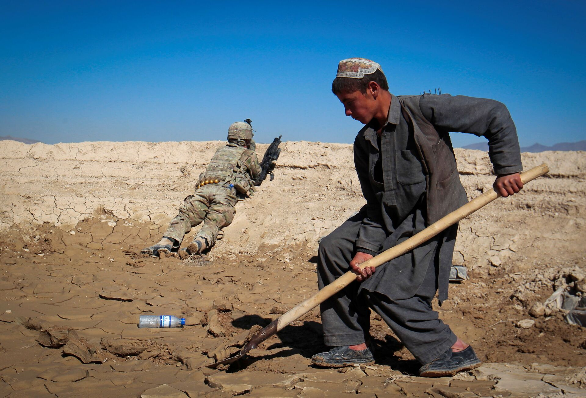 An Afghan boy works at a construction site as a U.S. Army soldier of 3/1 AD Task Force Bulldog takes position during a joint patrol with Afghan National Army (ANA) in a village in Kherwar district in Logar province, eastern Afghanistan, May 23, 2012.  - Sputnik International, 1920, 07.09.2021