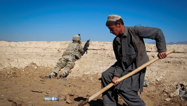 An Afghan boy works at a construction site as a U.S. Army soldier of 3/1 AD Task Force Bulldog takes position during a joint patrol with Afghan National Army (ANA) in a village in Kherwar district in Logar province, eastern Afghanistan, May 23, 2012.  - Sputnik International