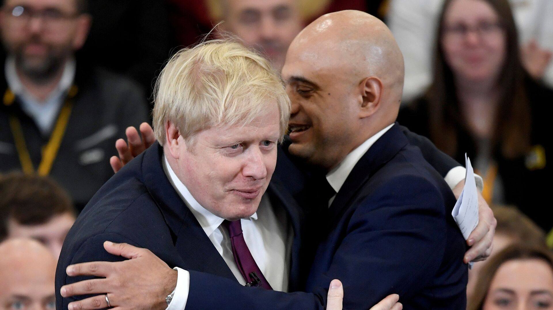 Britain's Prime Minister Boris Johnson is embraced by Britain's Chancellor of the Exchequer Sajid Javid before speaking to the workers as he visits a JCB factory during his general election campaign in Uttoxeter, Britain, December 10, 2019 - Sputnik International, 1920, 25.07.2021
