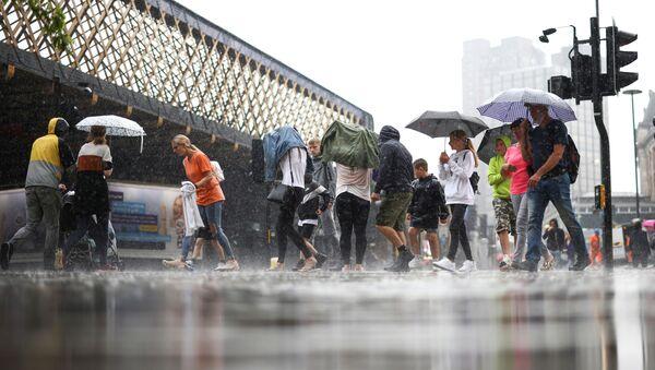 People walk through heavy rainfall, amid the coronavirus disease (COVID-19) outbreak, in London, Britain, July 25, 2021. - Sputnik International